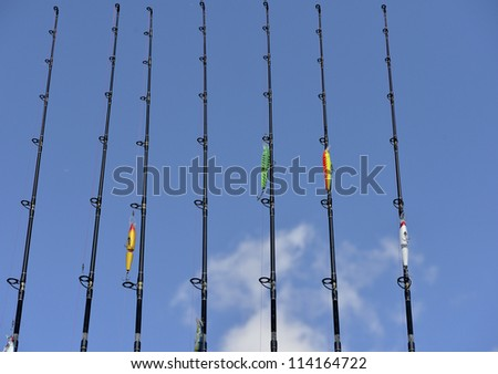 A group of fishing poles ready for use,  blue  sky - stock photo