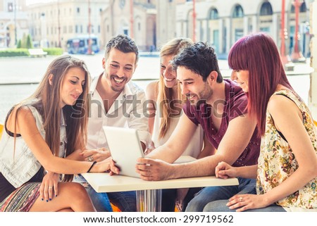 A group of five young friends (two men and three women) looking at a tablet sitting together at a table in a bar in the arcades in a hot summer day - stock photo