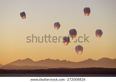 A group of flying lanterns being released into the nightsky