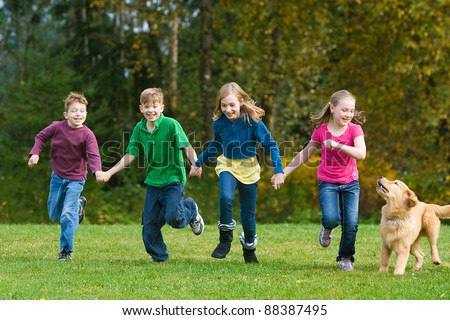 A group of four children holding hands and running together in a field. - stock photo