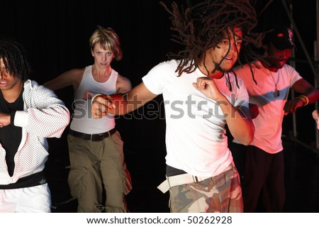 A group of four female and male freestyle hip-hop dancers during dance training session on stage. Lit with spotlights