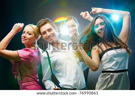 A group of four friends dancing and looking at camera - stock photo
