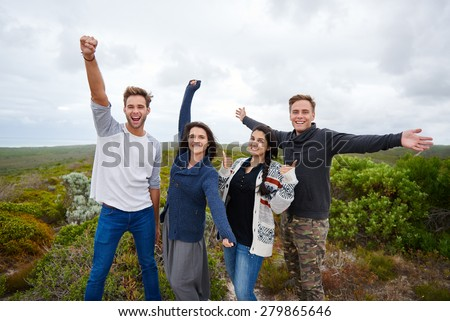 A group of four friends, mixed male and female, smiling at the camera and expressing their joy to be on a nature walk together on a pleasant overcast day - stock photo