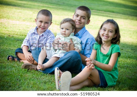 A group of four kids with one girl and three boys.  Brothers and sisters getting along nicely.  Shallow depth of field with sharp focus on the boys.