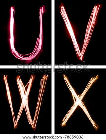 A group of four letters, written beam of light in total darkness. - stock photo