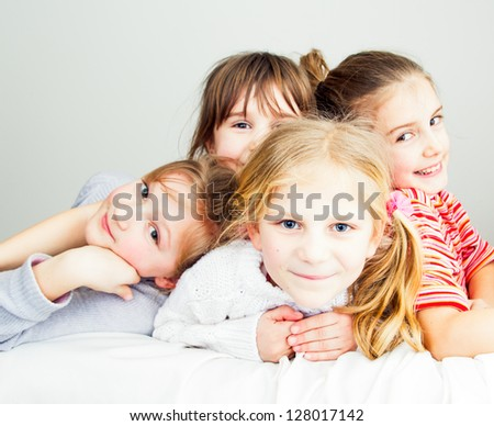 A group of four little girls have a fun and posing together - looking at camera
