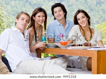 A group of four young adults sitting together to enjoy a meal with drinks outdoors - stock photo