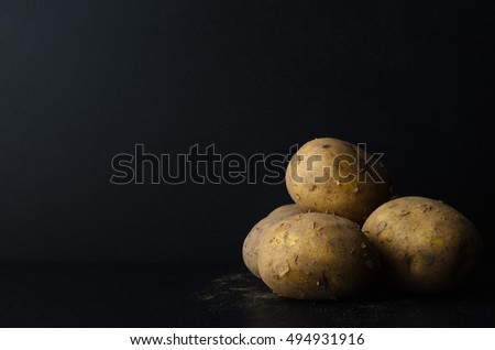 A group of freshly harvested, whole, unpeeled potatoes on black slate with a dusting of soil.  Black chalkboard background provides copy space.