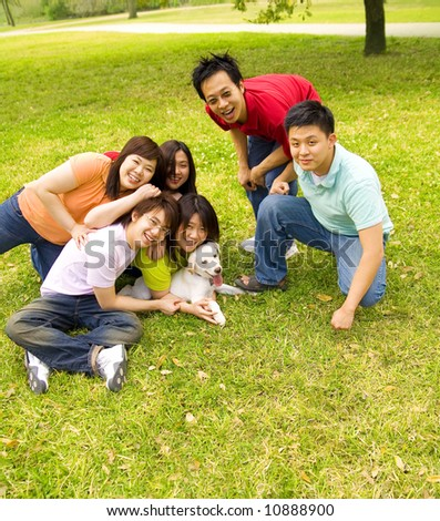 a group of friend playing and having fun on grass outdoor on grass with puppy labrador - stock photo