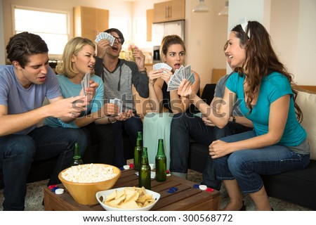 A group of friends college students young adults together playing poker cards  - stock photo