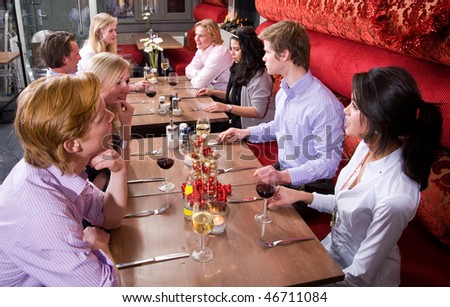 A group of friends having dinner at a restaurant - stock photo