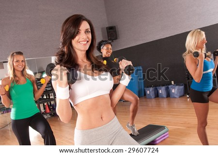 a group of friends in a step fitness class with the front girl in sharpest focus