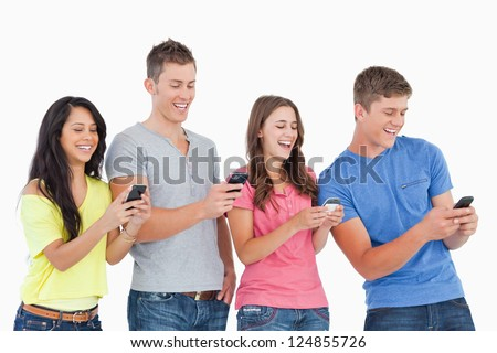 A group of friends laughing as they all send texts with their phones - stock photo