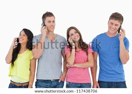 A group of friends on their phones making calls as they smile and stand beside each other - stock photo