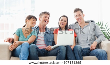 A group of friends sit on the couch together with their laptop as they laugh and watch the screen