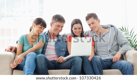 A group of friends sit together on the couch watching the laptop while smiling
