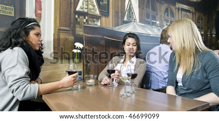 A group of girls having a drink in a cafe - stock photo