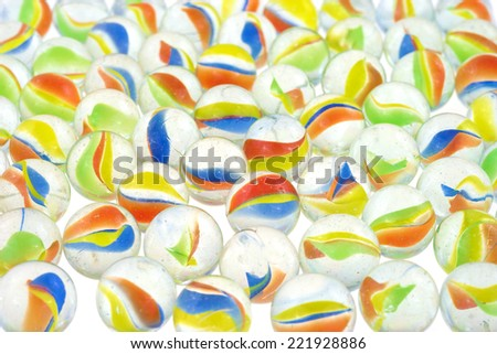 A group of glass marbles on a white illuminated surface. - stock photo