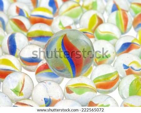 A group of glass marbles with a large marble atop on a white illuminated surface. - stock photo