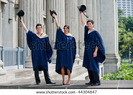 A group of graduates toss their mortar boards into the air - stock photo