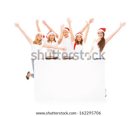 A group of happy and emotional teenagers in Christmas hats posing near a large blank banner - stock photo