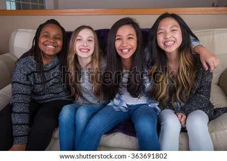 A group of happy kids sitting on a couch at home - stock photo
