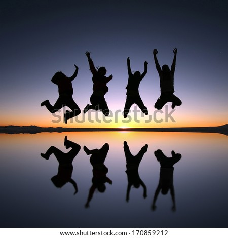 A group of happy young friends jumping in Solar de Uyuni, Bolivia