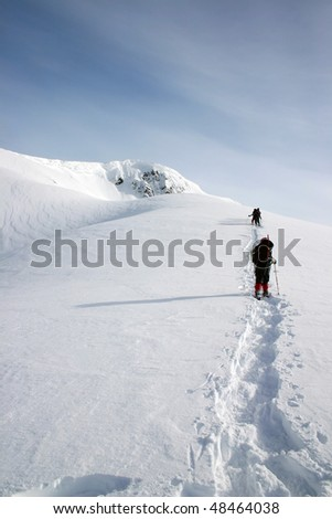 A group of hikers arrived the pass towards the snow peak during snowshoeing near BC, Canada.