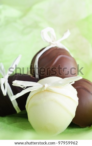 A group of home made egg shaped Easter chocolates, bow tied with raffia ribbon on a fresh, light Spring green background. - stock photo