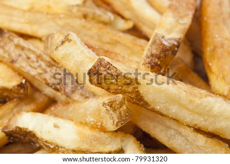 A group of hot french fries against a white background - stock photo