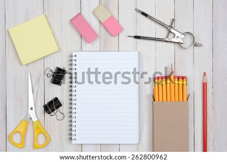A group of items typically found in a school desk. Items include: erasers, pencils, compass, scissors, paper, note pad, paper clips, shot from a high angle. - stock photo
