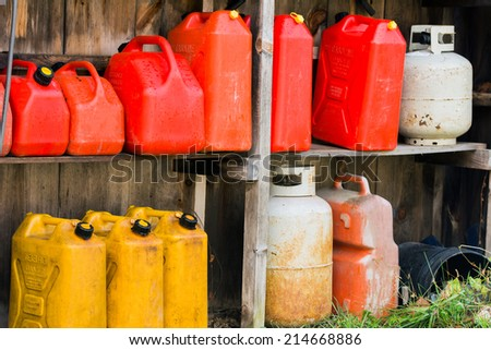 A group of jerry cans and propane tanks sit on shelves in a wooden shed.  - stock photo