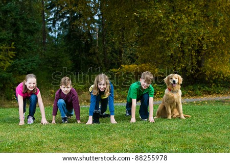 A group of 4 kids racing in a park with a dog. - stock photo