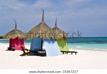A group of luxury colorful palapas on a pristine white sand beach, in the Caribbean. - stock photo
