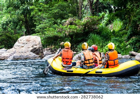 A group of men and women are rafting on the river, extreme and fun sport - stock photo