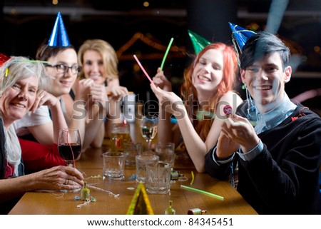 A group of men and women of mixed ages, wearing party hats and popping streamers. All are looking to the camera, one male is firing the streamers towards camera - stock photo