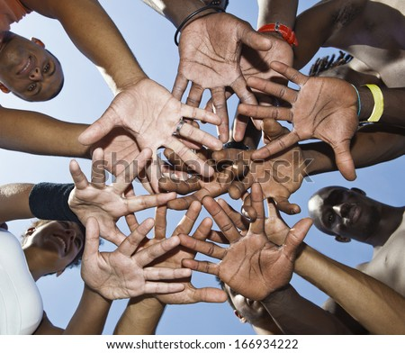 A group of mixed race people putting hands together
