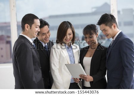 A group of muliethnic Business people using a digital tablet in the office. - stock photo