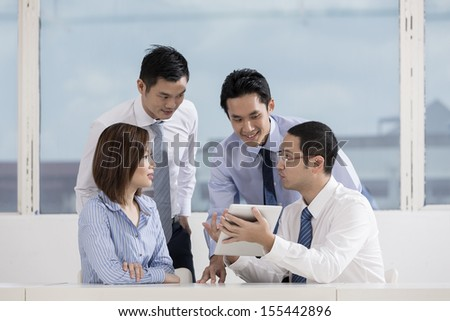 A group of muliethnic Business people working together. Using a digital tablet in the office. - stock photo
