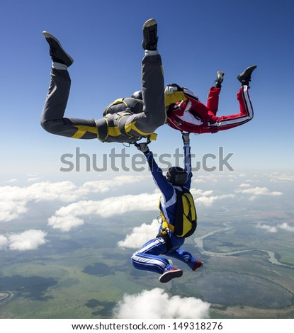 A group of paratroopers in a free style free fall. - stock photo