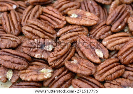 a group of pecan halves on flat for background uses - stock photo