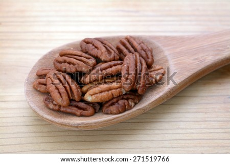 a group of pecan halves on wooden spoon on table  - stock photo
