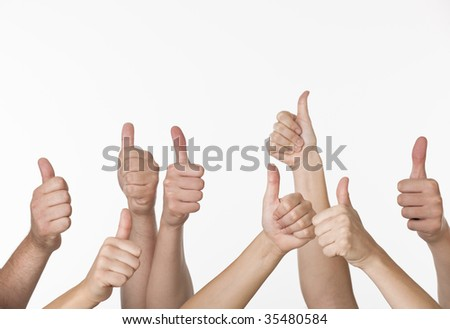 A group of people are giving thumbs-up signs.  Horizontally framed shot.