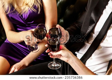 A group of people at a party making  cheer glasses of wine - stock photo