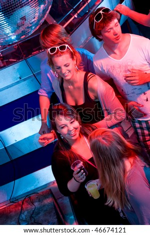 A group of people enjoying a party in a nightclub. - stock photo