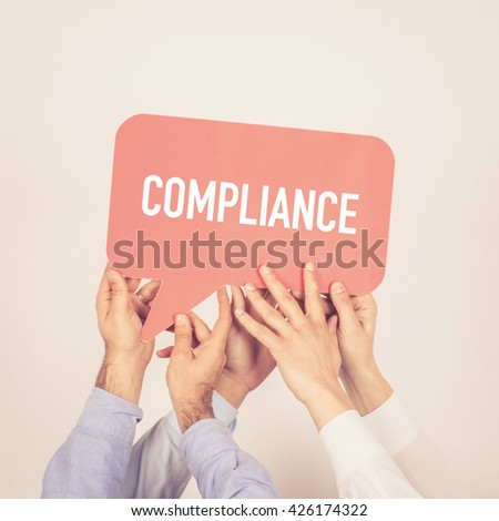 A group of people holding the Compliance written speech bubble - stock photo