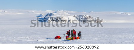 a group of people on winter expedition on ski with sled in wilderness mountainous landscape - panoramic view - stock photo