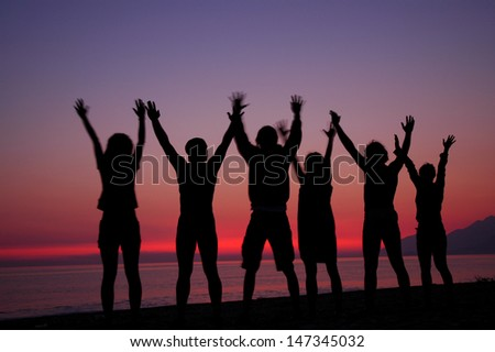 A group of people silhouettes in sunset  - stock photo