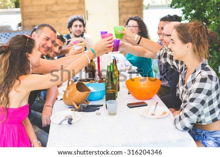 A group of people sitting on the table having lunch. A multicultural group of friends is toasting while they are eating. They are having fun together. Everybody is wearing summer clothes. - stock photo