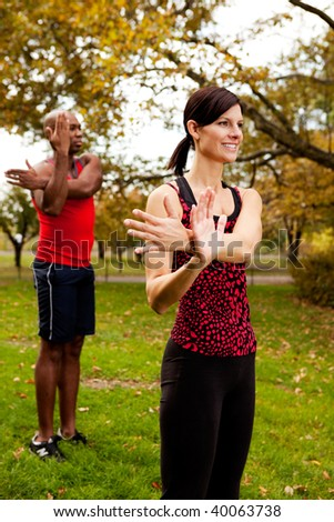 A group of people stretching in the park - stock photo